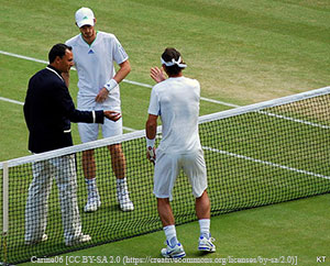 An umpire in a black coat flips a coin at the tennis net between to tennis players dressed in white.